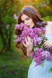 Härligt anseende för ung kvinna i trädgården med en filial av li royaltyfria foton