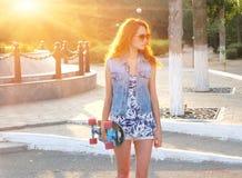 Härligt anseende för ung kvinna med skateboarden i henne händer Arkivfoto