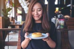 Härligt asiatiskt kvinnainnehav och visning en platta av munken med mening lycklig och bra livsstil i det moderna kafét arkivfoto