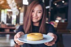 Härligt asiatiskt kvinnainnehav och visning en platta av munken med mening lycklig och bra livsstil i det moderna kafét arkivbilder