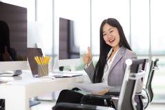 Härligt asiatiskt sammanträde för affärskvinna och le på stol i M royaltyfria foton