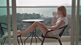 Härligt attraktivt kvinnasammanträde på balkongstol som kopplar av tycka om sikten Dricka te från koppen stock video
