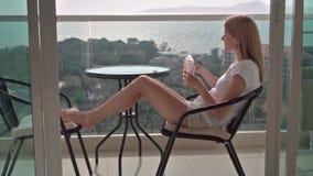Härligt attraktivt kvinnasammanträde på balkongstol som kopplar av tycka om sikten dricksvatten lager videofilmer