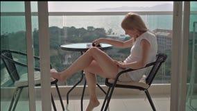 Härligt attraktivt kvinnasammanträde på balkongstol som tycker om sikten Stå upp och går inom arkivfilmer