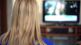 Härligt attraktivt kvinnasammanträde på soffan och hållande ögonen på TV Koppla kanaler med fjärrkontroll lager videofilmer