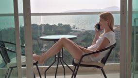 Härligt attraktivt sammanträde för ung kvinna på balkongstol som talar på smartphonen med vännen lager videofilmer
