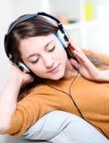 Härligt avkopplat lyssna för ung kvinna av musiken genom att vara le Arkivbilder