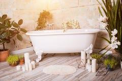 Härligt badrum med badet, blommor och stearinljus hemma royaltyfri fotografi