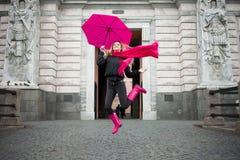 Härligt barn och lycklig blond kvinna med det färgrika paraplyet på gatan Begreppet av positivity och optimism arkivbild