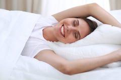 Härligt barn och lycklig kvinna som sover, medan ligga i säng bekvämt och le lyckligt royaltyfri bild