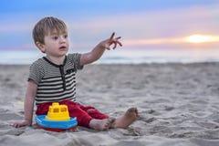Härligt barn på stranden på solnedgången Arkivfoton