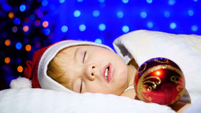 Härligt behandla som ett barn att sova på sängjulnatten I bakgrunden, ljusen och girlanderna av gran Arkivfoton