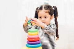 Härligt behandla som ett barn flickadagiset som spelar öglasleksakutbildning royaltyfri foto