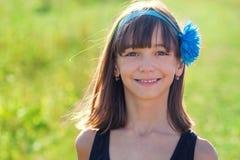 Härligt behandla som ett barn flickamodellen i sommar på en bakgrund av ett fält med en blomma på hennes huvud, royaltyfria bilder