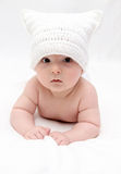 Spädbarn i vithatt ligger på säng Royaltyfri Fotografi