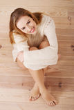 Härligt bekymmerslöst ungt tillfälligt kvinnasammanträde på golvet. Royaltyfri Bild