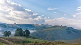 Härligt berglandskap av en dimmig morgon med och ett gamla hus, träd och moln Royaltyfri Bild