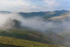 Härligt berglandskap av en dimmig morgon med och ett gamla hus, träd och moln Royaltyfria Foton