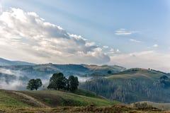 Härligt berglandskap av en dimmig morgon med och ett gamla hus, träd och moln Royaltyfri Foto