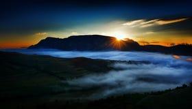 Härligt berglandskap i den dimmiga morgonen i album, Rumänien Fotografering för Bildbyråer