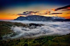 Härligt berglandskap i dimmig morgon i Rumänien Arkivbild