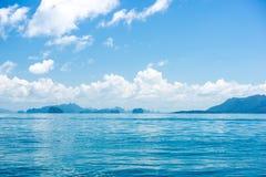 Härligt blått tropiskt havlandskap och moln med öar, Arkivbilder