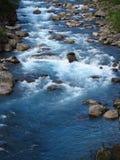 Härligt blått vatten i floden i den gröna vallen royaltyfri fotografi