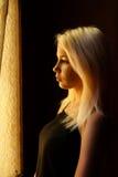 härligt blont flickabarn Dramatisk stående av en kvinna i mörkret Drömlik kvinnlig blick i skymning Kvinnlig silhouette royaltyfri foto