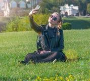 Härligt blont flickasammanträde på en grön gräsmatta och gör selfie Arkivfoto