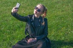 Härligt blont flickasammanträde på en grön gräsmatta och gör selfie Fotografering för Bildbyråer