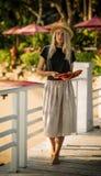 Härligt blont gå på morgonstranden med gulingsidor i hennes händer Bär en sugrörhatt, lång kjol och svärtar t Arkivbild