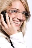 Härligt blont i exponeringsglas som pratar på hennes mobil arkivbilder