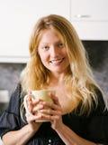 Härligt blont innehav ett stort kaffe Arkivbild