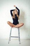 Härligt blont kvinnamodellsammanträde på en stol hår long royaltyfri fotografi