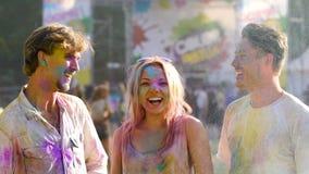 Härligt blont kvinnligt kasta handfullfärgpulver i luft som tycker om liv stock video