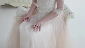 Härligt brudsammanträde på en stol, ett frodigt snör åt kjolcloseupen Handlagkjolhänder bröllop för klänningfragmentbeställning stock video