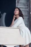 Härligt brunettflickaanseende på ett piano Royaltyfria Foton