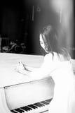 Härligt brunettflickaanseende på ett piano Arkivbilder