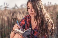 Härligt brunettflickafält, skjorta Nya idéer för begrepp som skriver i anteckningsbok En kvinna skriver i en anteckningsbok _ Arkivfoton