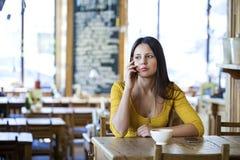 Härligt brunettflickasammanträde i en coffee shop royaltyfri fotografi