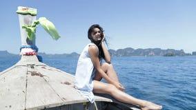 Härligt brunettkvinnasammanträde på lyckligt le för Thailand fartygnäsa, ung sexig flicka över havslandskap lager videofilmer