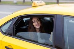 Härligt brunettsammanträde i gul taxi med det öppna fönstret arkivfoton