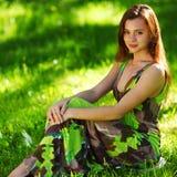 Brunettsammanträde på grönt gräs royaltyfri foto