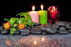 Härligt brunnsortbegrepp av den blommande blomman, stearinljus och den svarta stoen Fotografering för Bildbyråer