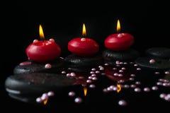 Härligt brunnsortbegrepp av stearinljus, zenstenar med droppar Royaltyfria Foton