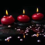 Härligt brunnsortbegrepp av stearinljus, zenstenar med droppar Royaltyfri Fotografi