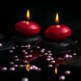 Härligt brunnsortbegrepp av stearinljus, zenstenar med droppar Arkivfoto