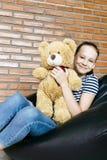 Härligt caucasian tonårigt flickasammanträde i stol för påse för svart böna som rymmer den stora bruna leksaken för nallebjörn oc royaltyfri bild