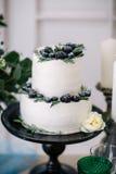 Härligt dekorera bröllopstårtan med stearinljus och blommor royaltyfri bild