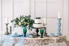 Härligt dekorera tabellen med stearinljus och bröllopstårtan i studio arkivbild